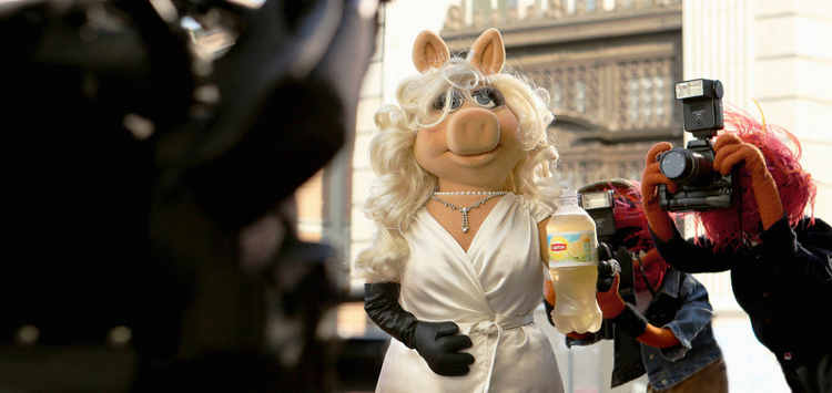 """Miss Piggy―diva, fashion icon and star of Disney's """"Muppets Most Wanted""""―is photographed by paparazzi (aka Animal) during the filming of Lipton's """"Be More Tea"""" ad, debuting during the Academy Awards, March 2, 2014."""