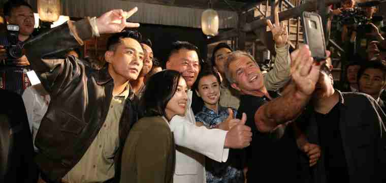 Dr. Shi Jianxiang and Mel Gibson taking a selfie at the conference with Chinese actor Liu Ye and other cast members