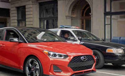 "In the Hyundai ad, ""Stoplight Standoff,"" two police officers and a Veloster driver exchange in a very awkward standoff."